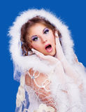 Surprised woman. Wearing a fur-coat, isolated against blue background, winter topic Stock Images