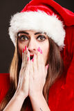 Surprised woman wearing santa claus hat. Christmas time. Young woman wearing santa claus hat red dress on black background. Surprised face expression Stock Images