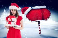 Surprised woman wearing santa hat holding stack of gifts Stock Photo
