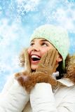 Surprised woman in winter clothes. Pleasantly surprised young woman smiles looking up Royalty Free Stock Photo