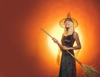 Surprised woman in witches hat and costume on red Halloween background. Beauty Woman posing with Pumpkin and Halloween. Hat. Witch vampire concept. Halloween royalty free stock photography