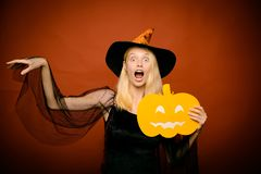 Surprised woman in witches hat and costume on red Halloween background. Pumpkin head jack lantern. Beautiful young. Surprised woman in witches hat pointing hand royalty free stock photo