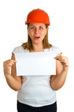 Surprised women in a red helmet with paper. Surprised young women in a red building helmet with a sheet of paper in a hand. Isolation on a white background Stock Photography