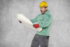 Surprised worker can not read construction plans. Protective helmet on the head Royalty Free Stock Photo