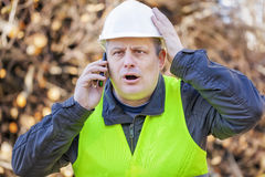 Surprised worker with cell phone Royalty Free Stock Photos