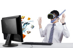 Surprised worker looking at fishes on monitor. Suprised businessman looking at fishes on the monitor while wearing goggles and snorkel, isolated on white Stock Photo