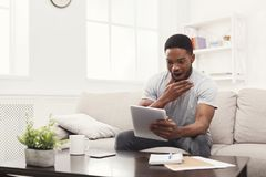 Surprised young man at home reading on tablet Royalty Free Stock Images