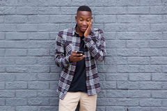 Surprised young african guy looking at cell phone Stock Image