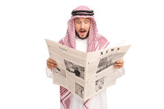 Surprised young Arab reading a newspaper Royalty Free Stock Photo