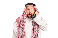 Surprised young Arab speaking on telephone royalty free stock photography