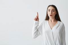 Surprised young beautiful businesswoman with opened mouth pointing finger up over white background. royalty free stock photos