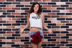 Surprised young beautiful woman with roses between her legs Stock Image
