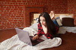 Surprised young beautiful woman shopping online in bed using modern laptop Stock Image