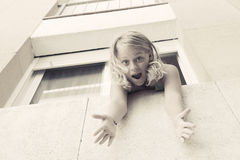 Surprised young blond Caucasian girl in the window Royalty Free Stock Photo
