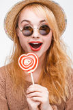 Surprised young blonde in sunglasses with lollipop. Surprised young happy blonde in sunglasses and straw hat with lollipop. Fashionable nice young hipster woman Royalty Free Stock Photo