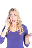 Surprised Young Blonde Woman Talking on Cell Phone Stock Photo