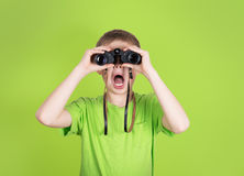 Surprised young boy with binoculars on green background. Shocked Stock Image