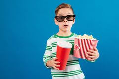 Surprised young boy in eyeglasses preparing to watch the film Royalty Free Stock Image