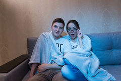 Surprised young boy and girl in glasses snuggling up watching te. Surprised young boy and girl in glasses snuggling up together under a blanket on a sofa at home Stock Images