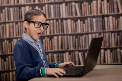 Surprised young  boy in the library with computer Stock Photos