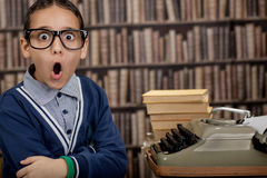 Surprised young  boy in the library with typewriter Royalty Free Stock Photos