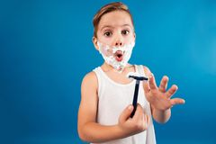 Surprised young boy in shaving foam like man holding razor Stock Photo
