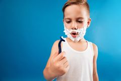 Surprised young boy in shaving foam looking at razor Stock Photo
