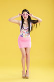 Surprised young brunette woman in pink skirt and tank top on yellow background. funny girl with pink sunglasses Royalty Free Stock Photos