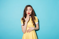 Surprised young brunette woman in yellow dress Stock Images