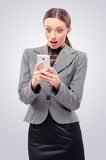 Surprised young business woman holding mobile phone Royalty Free Stock Photo