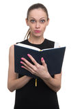 Surprised young business woman looking at diary Royalty Free Stock Image