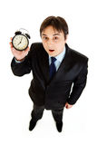 Surprised young businessman holding alarm clock Stock Photo