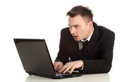 Surprised young businessman working on laptop Stock Photo