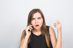 Surprised young businesswoman talking on the mobile phone. And pointing finger away isolated on a white background Royalty Free Stock Images