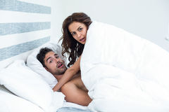 Surprised young couple enjoying on bed Royalty Free Stock Photo