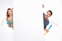 Surprised young couple with paint rollers and blank card looking at camera Royalty Free Stock Photography