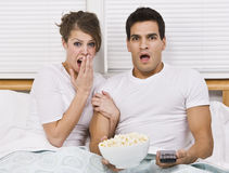Surprised Young Couple Watching TV. A young, attractive couple is sitting together in bed and watching TV.  They look shocked or scared, and are looking away Stock Photo