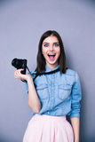 Surprised young cute woman holding camera Royalty Free Stock Images