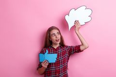 A surprised girl holding a image of a thought or an idea and a thumbs up sign and looking away. stock photography