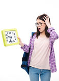 Surprised young female student looking on clock Stock Photos