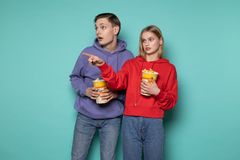 Surprised young friends, blonde girl in red hoodie and his friend in purple hoodie with popcorn in hands pointing at stock photos
