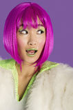 Surprised young funky woman in pink wig looking sideways over purple background Stock Images