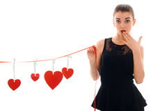 Surprised a young girl in a black dress covers her mouth and hand holds a Red Ribbon with hearts. Isolated on white background Royalty Free Stock Photo