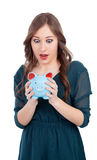 Surprised young girl with a blue money-box Stock Photos