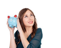 Surprised young girl with a blue money-box Royalty Free Stock Image