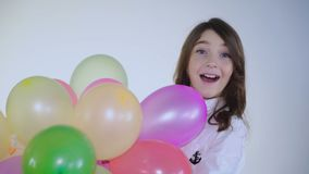 Surprised young girl catches balloons and looks at camera on background