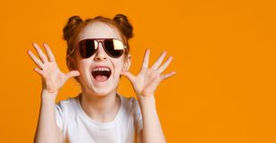 Surprised young girl in glasses over yellow background stock photo