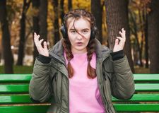 Surprised young girl with headphones. A teenage girl on a park bench in autumn Royalty Free Stock Image