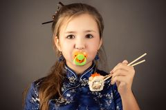 Surprised young girl with pacifier in mouth and roll in hands stock image