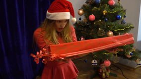 Surprised young girl in santa hat with big long christmas gift stock video footage